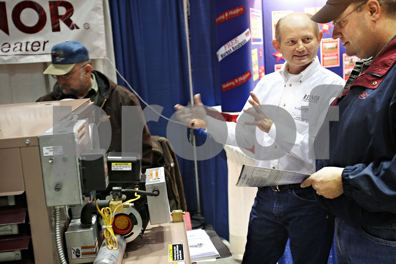 Beck Diefenbach  -  bdiefenbach@daily-chronicle.com<br /> <br /> Farmer John Gustafson (far right), of Byron, Ill., listens to Kevin Cochran, of Model Marketing, explain the mechanics behind the Reznor Used Oil Heater during the 27th Annual Northern Illinois Farm Show at the Northern Illinois University Convocation Center in DeKalb, Ill., on Wednesday Jan. 7, 2009. Used oil heaters helps farmers save money by using less natural gas and not having to pay to get rid of the spent oil.