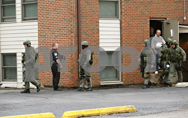 Beck Diefenbach  -  bdiefenbach@daily-chronicle.com<br /> <br /> State police officers exit an apartment building on the 800 block of Kimberly Drive following an early morning stand off in DeKalb, Illl., on Wednesday May 27, 2009.