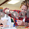 Beck Diefenbach  -  bdiefenbach@daily-chronicle.com<br /> <br /> Center, Christa Kennett, senior at Northern Illinois University, assembles the gear box to a solar powered plastic toy crab during a workshop combining solar power and art as part of the NIU Women's Studies Program at the Holmes Student Center at NIU in DeKalb, Ill., on Tuesday March 17, 2009.