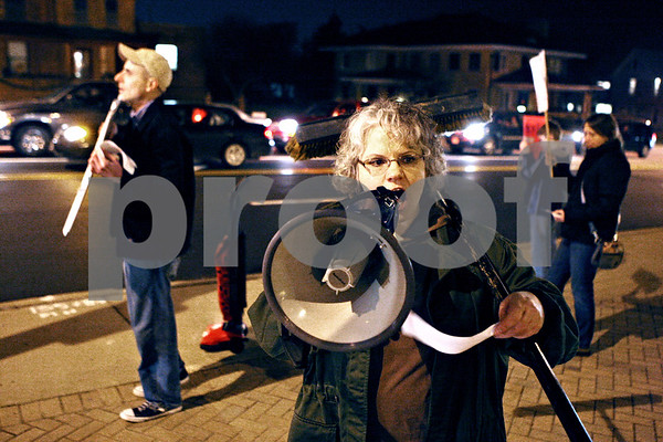 Rob Winner – rwinner@daily-chronicle.com<br /> Lynn Fazekas uses a megaphone to begin a protest chant on the northeast corner of Lincoln Highway and First Street in DeKalb on Monday evening.<br /> 11/23/2009