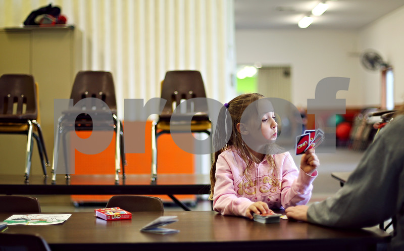 Beck Diefenbach  -  bdiefenbach@daily-chronicle.com<br /> <br /> Hope Dobzynski, 6, inspects her hand while playing the Uno card game with her camp counselor Justine Ingoldsby during the Kids Klub spring break program at the Genoa Park District building in Genoa, Ill., on Monday March 23, 2009.