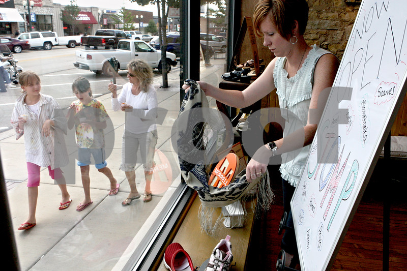 Rob Winner – rwinner@daily-chronicle.com<br /> Stephanie Comer straightens up the product in the front window of Stomp in downtown Sycamore on Wednesday afternoon. Stomp is a new shoe store wrapping up its first month in the location that housed family-owned Downtown Shoes for 50 years.<br /> 07/29/2009