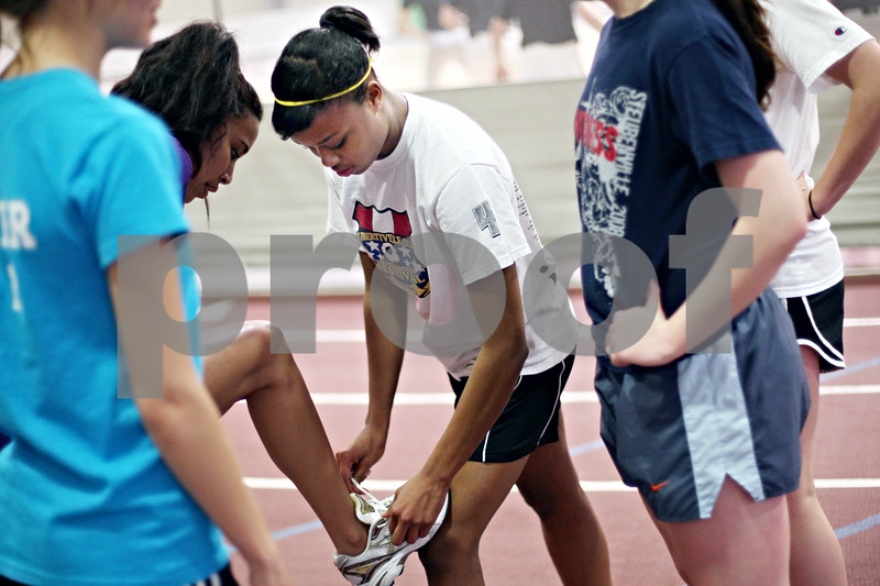 Beck Diefenbach  -  bdiefenbach@daily-chronicle.com<br /> <br /> Sycamore track runner Lake Kwaza helps tie a teammate shoe between sprints during practice at Sycamore High School's field house in Sycamore, Ill., on Monday April 13, 2009.