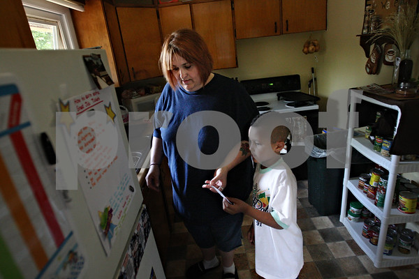 Beck Diefenbach  -  bdiefenbach@daily-chronicle.com<br /> <br /> Javon, 7, gives his mother Pamela Lick a ticket for 30 minutes of video game time at their DeKalb home on Friday August 14, 2009. Javon and his two brothers can receive video game time points by reading or doing other chores.
