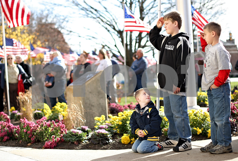 Beck Diefenbach  -  bdiefenbach@daily-chronicle.com<br /> <br /> Kneeling, Justin Forsberg, 2, watches his brothers Gavin, 10 (center), and Noah, 7, all of Sycamore, salute during the singing of the National Anthem in the opening of the Veteran's Day observation in front of the DeKalb County Courthouse in Sycamore, lll., on Nov. 11, 2009.
