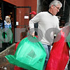 Rob Winner – rwinner@daily-chronicle.com<br /> At Blumen Gardens in Sycamore, Ill., Tom Doty, of Sycamore, helps carry bags filled with gifts to a volunteer's vehicle for distribution to families throughout the community on Thursday December 24, 2009. Over 800 gifts were distributed by Goodfellows, which is a volunteer group that delivers gifts to the needy during the holidays.