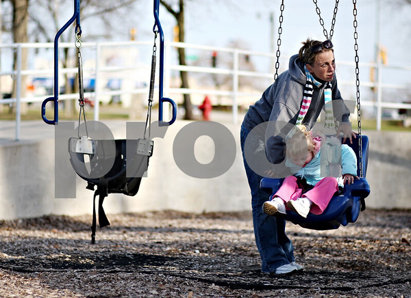 Beck Diefenbach  -  bdiefenbach@daily-chronicle.com<br /> <br /> Kelly Livingston, of Sycamore, helps her daughter Molly, 4, get out of a swing while playing at Hopkins Park in DeKalb, Ill., on Wednesday April 1, 2009. Livingston is on winter furlough from her job at the Garden Market.