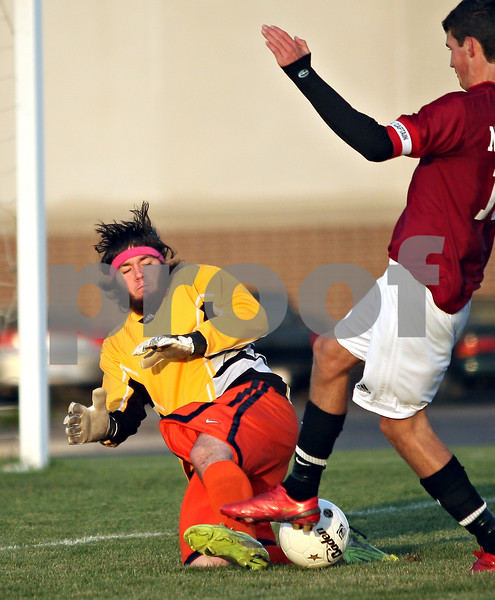 Beck Diefenbach  -  bdiefenbach@daily-chronicle.com<br /> <br /> Genoa-Kingston's goal keeper Taylor Rogers (left) slides to block a shot by Northridge's Bart Bak (10) during second half of the regional playoff game at GK High School in Genoa, Ill., on Tuesday Oct. 13, 2009. After two overtime periods, the game was suspended due to darkness and will be restarted on Thursday at 4:30 P.M. at Genoa-Kington High School.
