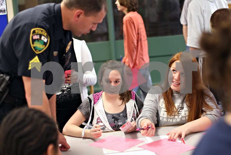 Beck Diefenbach  -  bdiefenbach@daily-chronicle.com<br /> <br /> Sycamore freshmen Kelly Culton (right) and Nicole Welton question Sycamore Police Sergeant at his booth during career day at Sycamore High School in Sycamore, Ill., on Thursday May 7, 2009.