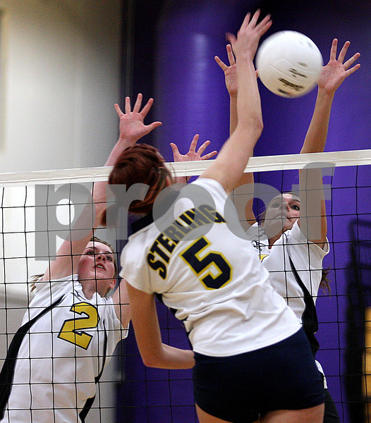 Rob Winner – rwinner@daily-chronicle.com<br /> Sycamore's Kate Binder (2) and Brittany Olson look to block a spike by Sterling's Keeley Knie in the first game.<br /> 11/03/2009