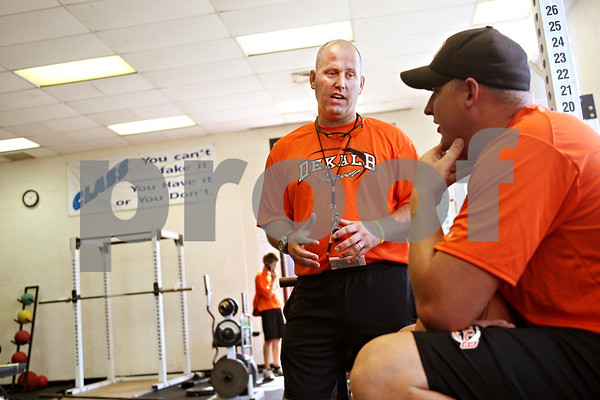 Beck Diefenbach  -  bdiefenbach@daily-chronicle.com<br /> <br /> DeKalb High School's new football head coach Marty Sanders talks with assistant coach Tim Vincent during the first day of practice at DeKalb High School in DeKalb, Ill., on Monday July 6, 2009.