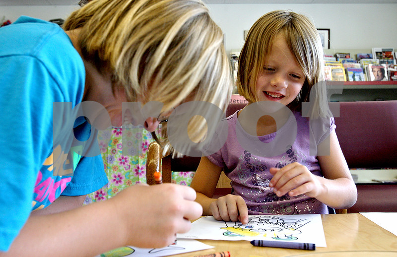 CQ<br /> Rob Winner – rwinner@daily-chronicle.com<br /> Erin Karasewski (left), 10, and her sister Taiylor, 7, spend some time coloring with crayons while visiting the Cortland Community Library on Tuesday afternoon.<br /> 07/07/2009