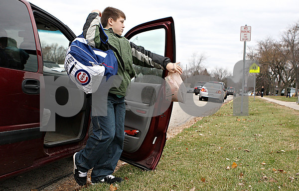 Rob Winner – rwinner@daily-chronicle.com<br /> Fifth grader Jake Perkins, 11, is dropped off in front of Lincoln Elementary School in DeKalb by his mother on Monday morning. Bus drivers for DeKalb School District 428 went on strike Monday morning after voting down a proposed contract from First Student.<br /> 11/16/2009