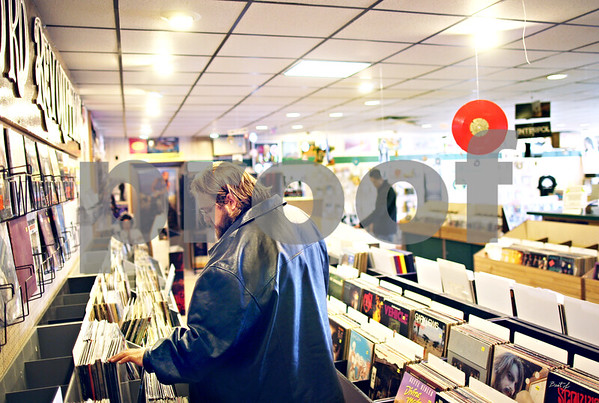 "Beck Diefenbach  -  bdiefenbach@daily-chronicle.com<br /> <br /> Tyler Wilson, of Marengo,searches through vinyl records at Record Rev in DeKalb, Ill., on Tuesday April 21, 2009. After 35 years, Record Rev is closing it's doors. ""Can't buy a vinyl (record) many too places anymore,"" Wilson said."