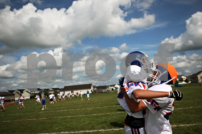 Beck Diefenbach  -  bdiefenbach@daily-chronicle.com<br /> <br /> Genoa-Kingston's Calvin Beach, left, is lifted up by Matt Falko during a tackling drills at practice at GK High school in Genoa, Ill., on Monday Aug. 17, 2009.