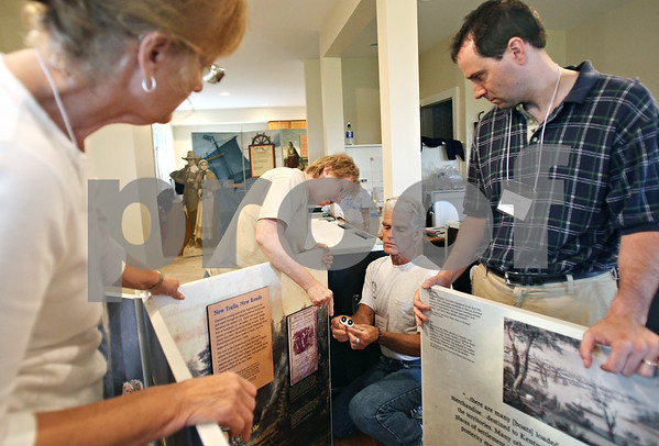 Beck Diefenbach  -  bdiefenbach@daily-chronicle.com<br /> <br /> Center left, Claudia Dant, of the Wabash County Museum, works with Mike Tappero (center right), of Hampton, to assemble one of the many displays from the Smithsonian Museum at the Sycamore Historical Museum in Sycamore, Ill., on Wednesday May 27, 2009.