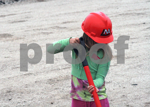Randi Stella – rstella@daily-chronicle.com<br /> <br /> 10 year old Tessa Wallace puts on a hard hat and digs into the ground near Dresser St. where the new DeKalb high school will be constructed on Wednesday May 27th. 2009.
