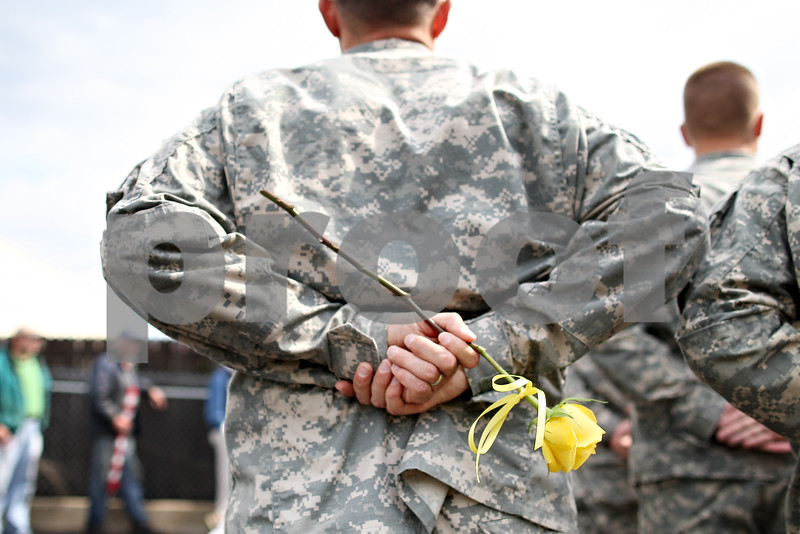 Beck Diefenbach  -  bdiefenbach@daily-chronicle.com<br /> <br /> A soldier with the Sycamore National Guard Unit holds a yellow rose upon returning to the Sycamore National Guard armory in Sycamore, Ill., on Monday June 1, 2009.