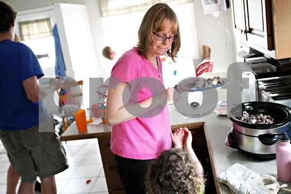 Beck Diefenbach  -  bdiefenbach@daily-chronicle.com<br /> <br /> Patty Ihm gives a snack to one of her two foster children while preparing dinner in their DeKalb home on Friday May 8, 2009. IHM also has four children of her own, one of which is adopted.