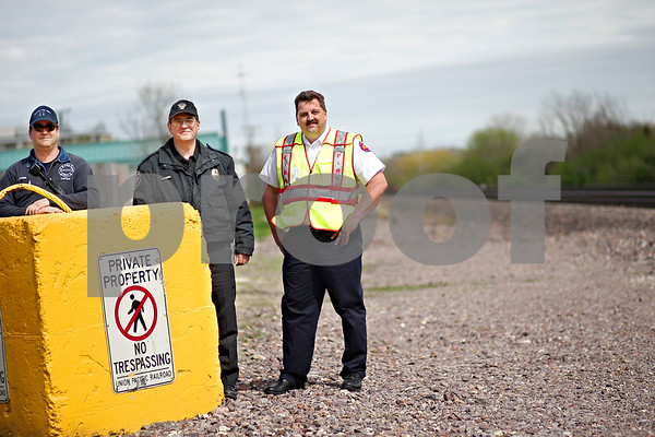 Beck Diefenbach  -  bdiefenbach@daily-chronicle.com<br /> <br /> From left, DeKalb Fire Captain Jim Zarek, Senior Special Agent for Public Safety of Union Pacific Police Department Jim Magner, and DeKalb Fire Chief Bruce Harrison stand by one of the large blocks used to curb illegal rail crossing by pedestrians in DeKalb, Ill.