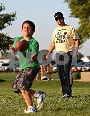 Beck Diefenbach  -  bdiefenbach@daily-chronicle.com<br /> <br /> Oscar Cornejo, of Dekalb, watches his son Vincent, 9, catch a ball while playing at Sycamore Park in Sycamore, Ill., on Thursday Sept. 10, 2009.