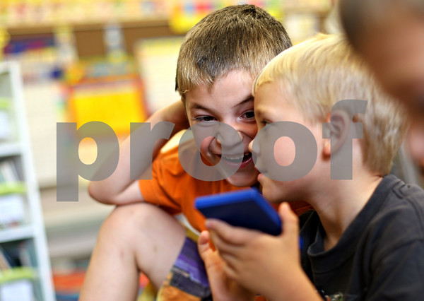 Beck Diefenbach  -  bdiefenbach@daily-chronicle.com<br /> <br /> North Elementary School kindergartners Derek Sandy, left, reacts as Cole Heidelmeier types numbers into his calculator during class in Sycamore, Ill., on Friday Sept. 25, 2009.