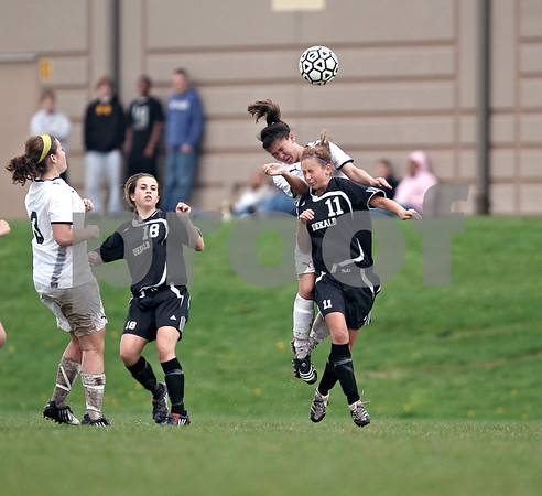 Beck Diefenbach  -  bdiefenbach@daily-chronicle.com<br /> <br /> DeKalb's Kasidi McKeon (11) and Sycamore's Emma Norris (7) both leap to head the ball during the second half of the game at Sycamore High School in Sycamore, Ill., on Thursday April 30, 2009. Sycamore beat DeKalb 4 to 0.