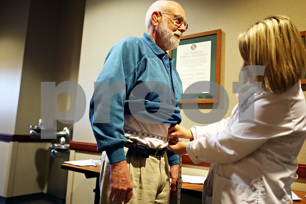 "Beck Diefenbach – bdiefenbach@daily-chronicle.com<br /> <br /> Ken Williams, of Sycamore, has the circumference of his waist measured by Lynn Fifer, Kishwaukee Hospital registered dietitian, for the first weigh-in for ""Weight No More,"" at Kishwaukee Hospital in DeKalb, Ill., on Monday March 2, 2009."