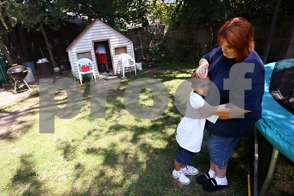 Beck Diefenbach  -  bdiefenbach@daily-chronicle.com<br /> <br /> Pamela Lick hugs one of her three sons, Javon outside of their DeKalb home on Friday August 14, 2009. Lick's family recently enacted a family contract and points system to help maintain a civil house.