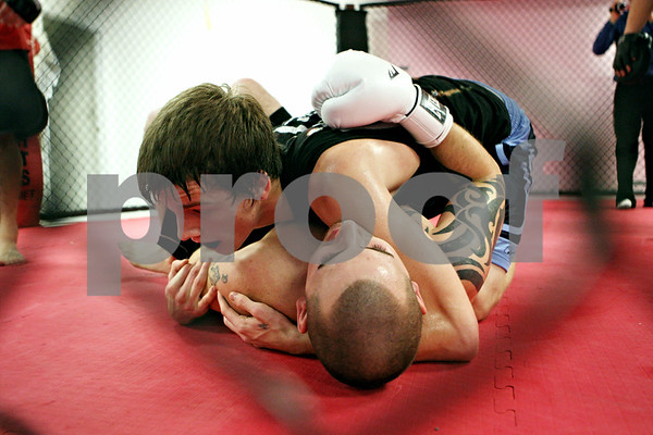 Rob Winner – rwinner@daily-chronicle.com<br /> Nick Parker (top), of Plano, and Jacob Brewick, of Sandwich, practice mixed martial arts within a cage at Power Martial Arts in Plano on Tuesday evening.<br /> 11/17/2009
