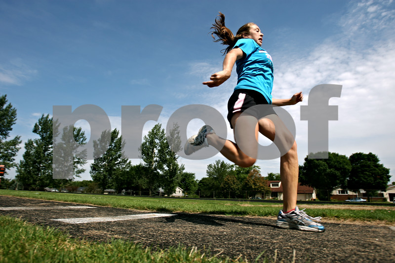 Rob Winner – rwinner@daily-chronicle.com<br /> Stephanie Milroy, 14, practices the triple jump during practice at DeKalb High School. Sisters Stephanie and Jen Milroy qualified for the Junior Olympic nationals with the Huskie Track Club.<br /> 07/24/2009