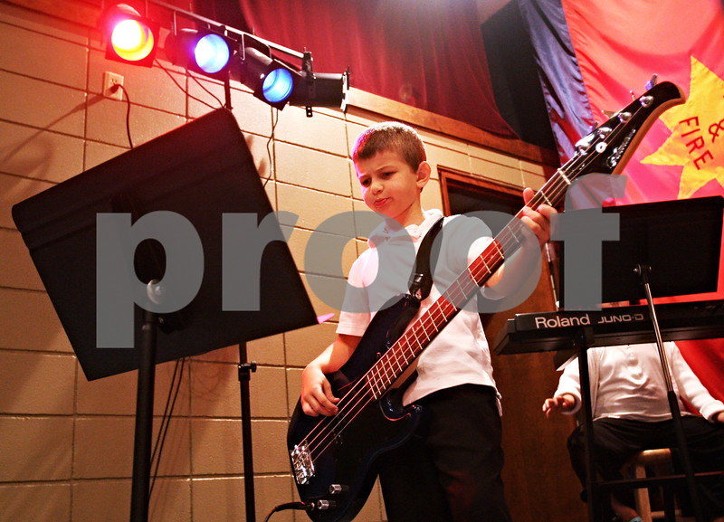 """Beck Diefenbach  -  bdiefenbach@daily-chronicle.com<br /> <br /> Noah Hansen, 8, plays bass during band practice for """"The Reborn"""" at the Salvation Army in DeKalb, Ill., on Wednesday Sept. 23, 2009."""