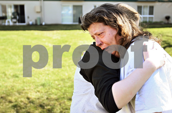 Beck Diefenbach  -  bdiefenbach@daily-chronicle.com<br /> <br /> Lynda McCall, right, is embraced by her neighbor Karyn Stoutenburg after McCall's apartment is damaged by a fire next to her apartment on the 600 block of Ridge Road in DeKalb, Ill., on Thursday April 16, 2009.