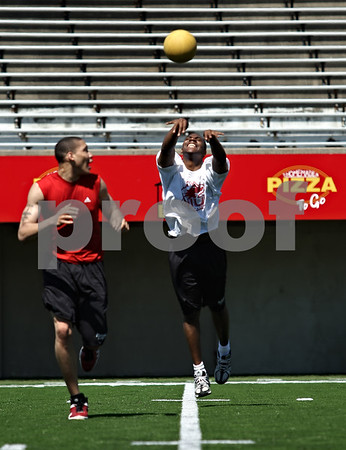 Beck Diefenbach  -  bdiefenbach@daily-chronicle.com<br /> <br /> Northern Illinois basketball player Jake Anderson, center, tosses a medicine ball with teammate Lee Fisher during off season training at Huskie Stadium in DeKalb, Ill., on Friday June 26, 2009.