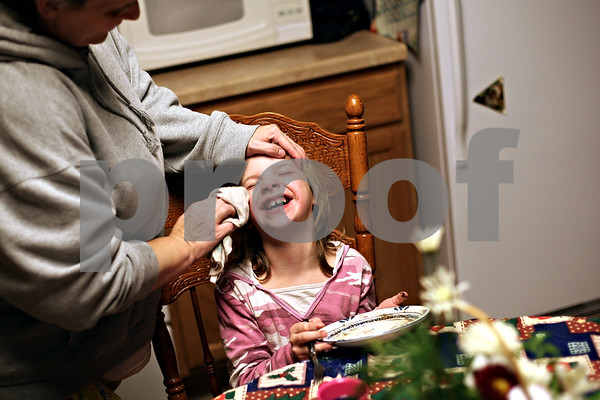 Beck Diefenbach  -  bdiefenbach@daily-chronicle.com<br /> <br /> Jada Edwards, 8, can't contain herself while her mother Deb wipes her face after eating some cake for dessert at their new home in DeKalb, Ill.,  on Monday Dec. 21, 2009. The Edwards family moved into their home just a week ago.