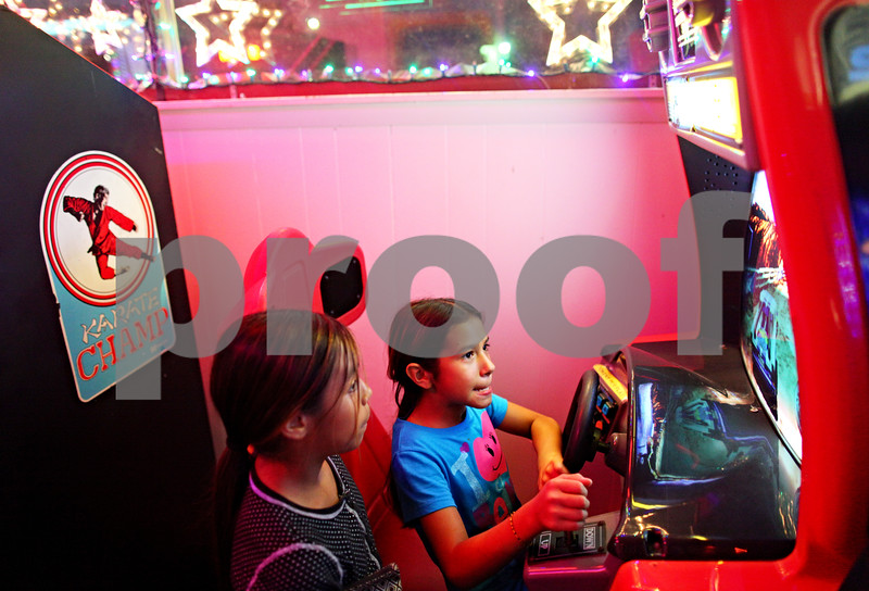 Beck Diefenbach  -  bdiefenbach@daily-chronicle.com<br /> <br /> Center, Brianna Pizano, 10, plays a driving game as Aurora Hurtado, 10, watches at Star Worlds Arcade in DeKalb, Ill., on Tuesday Aug. 25, 2009.