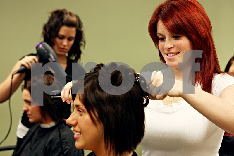 Rob Winner –  rwinner@daily-chronicle.com<br /> Tori Brantley (right) works on the hair of classmate Lauren Rzasa on Wednesday afternoon at the Hair Professionals Career College in Sycamore.<br /> 09/16/2009