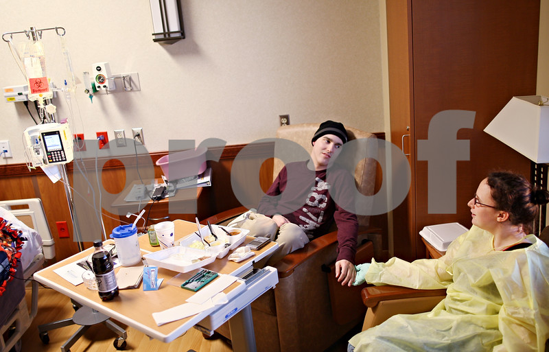 Beck Diefenbach  -  bdiefenbach@daily-chronicle.com<br /> <br /> Kevin holds the hand of his girlfriend Erika Sorg as he undergoes a round of Chemotherapy at Kishwaukee Community Hospital on Tuesday April 7, 2009.