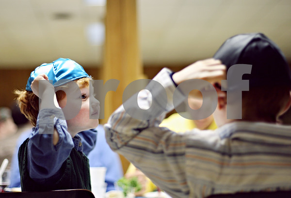 Beck Diefenbach  -  bdiefenbach@daily-chronicle.com<br /> <br /> From left, Cameron Kruskol, 4, of Sycamore, and his brother Kyle, 8, try on Yamikas during a Passover seder meal hosted by Congregation Beth Shalom in DeKalb, Ill., on Thursday April 9, 2009.
