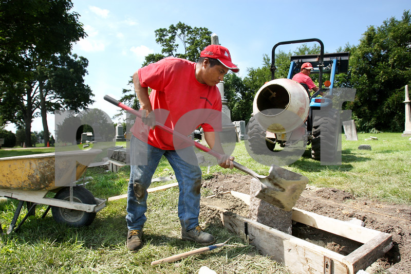 Rob Winner – rwinner@daily-chronicle.com<br /> Mario Gomez (left) and Marcelo Tepancatl, both of Image Monuments and Cemetery Services, pour a new foundation for a headstone at Elmwood Cemetery in Sycamore on Friday afternoon.<br /> 07/23/2009