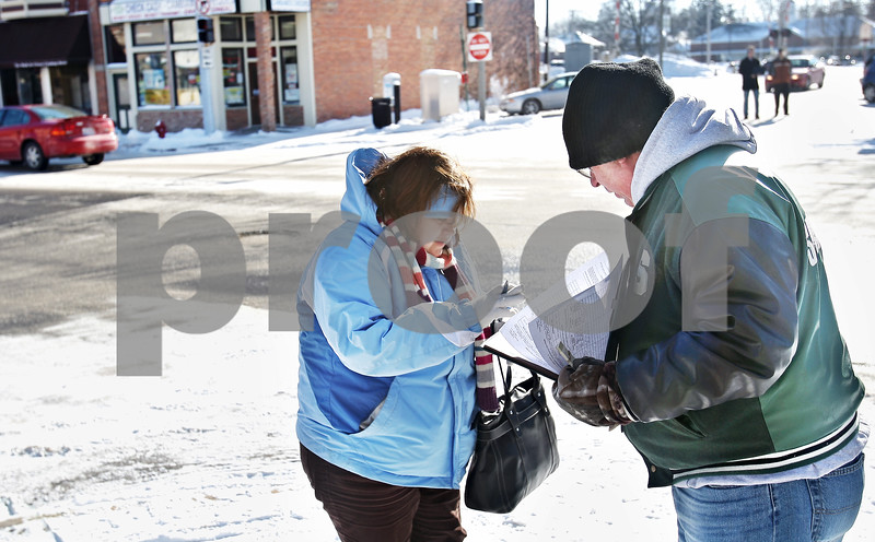 Beck Diefenbach  -  bdiefenbach@daily-chronicle.com<br /> <br /> Left, Diana Beams, of DeKalb, Ill., signs a petition by volunteer Ed Pevonka to add the independent mayoral candidate Lynn Fazekas to the ballot on the corner of 3rd Street and Lincoln Highway in DeKalb, Ill., on Friday Jan. 16, 2009.