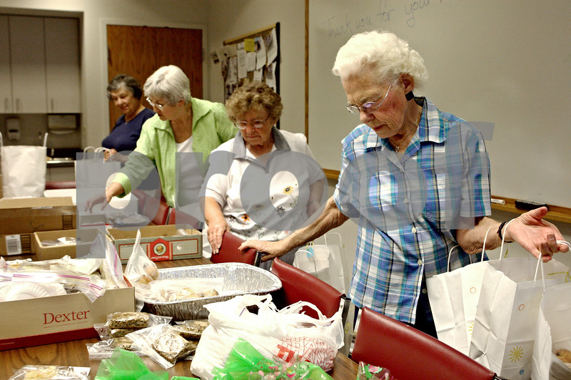 Rob Winner – rwinner@kcchronicle.com<br /> On Tuesday morning, volunteers including Jeanette Weeks (front to back), Barbara Yusunas, Jane Randolph and Karen Finn help package homemade baked goods to be distributed to patients and their caregivers at the DeKalb County Hospice.<br /> 07/21/2009<br /> Weeks and Yusunas are from Sycamore <br /> and<br /> Randolph and Finn are from DeKalb