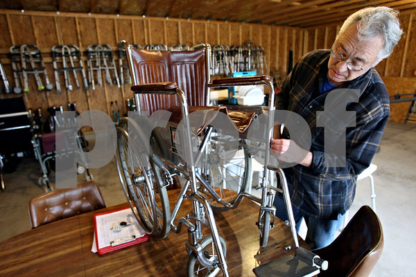 Rob Winner – rwinner@daily-chronicle.com<br /> Gary Pisarski looks over a wheel chair in need of repair at Mary's Lending Closet in Sycamore on Monday October 26, 2009. Mary's Lending closet is an outreach program of St. John's Lutheran Church and operates out of a garage on the church's property.