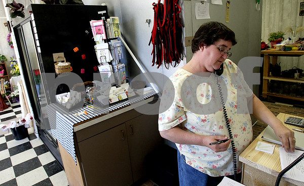 Rob Winner – rwinner@daily-chronicle.com<br /> Owner Tina Johnson of Duttons and Bows floral shop in Shabbona takes a call while in the process of getting the shop in order on Friday morning.<br /> 04/24/2009