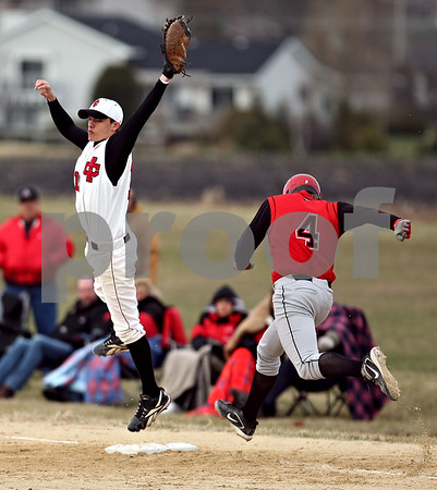 Beck Diefenbach  -  bdiefenbach@daily-chronicle.com<br /> <br /> Amboy's Jeremy Wolf (4) is safe at first as Indian Creek's Trevor Foster (10) leaps to catch the ball during the top of the second inning of the game at Indian Creek High School in Shabbona, Ill., on Friday March 27, 2009.