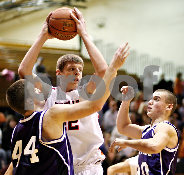 Beck Diefenbach  -  bdiefenbach@daily-chronicle.com<br /> <br /> DeKalb's Jordan Threloff (42, center) looks to pass the ball while defended by Hampshire's Tyler Watzlawick (44, left) and Pat Dumoulin (30,right) during the fourth quarter of the game at DeKalb High School on Tuesday Dec. 22, 2009. DeKalb defeated Hampshire 58 to 50.