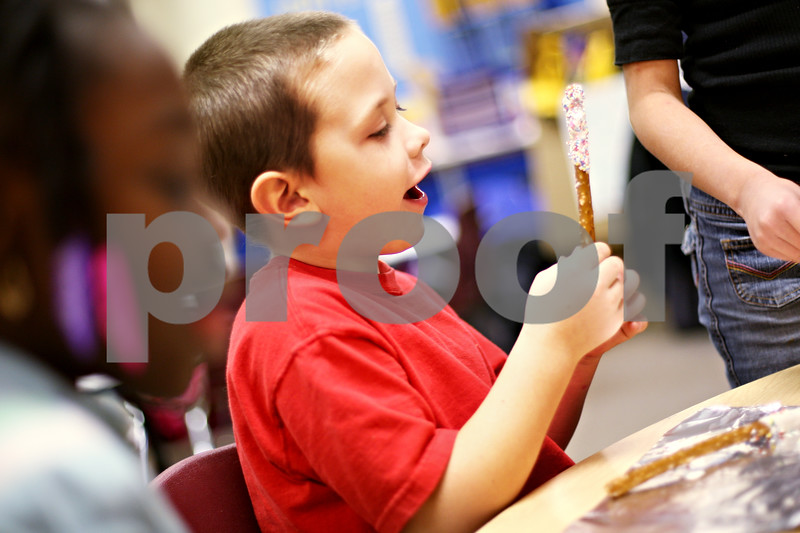 Beck Diefenbach  -  bdiefenbach@daily-chronicle.com<br /> <br /> Kindergartner Ethan Wascher makes a candy pretzel stick during an after school program run in conjunction with the YMCA at Little John Elementary School on Tuesday Dec. 15, 2009.