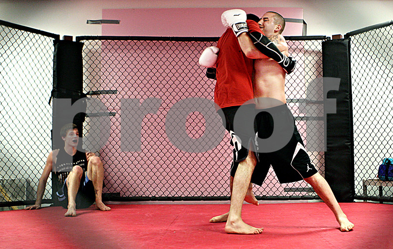 Rob Winner – rwinner@daily-chronicle.com<br /> (From left to right) Nick Parker, of Plano, watches as Zach Neill, of Aurora,  and Jacob Brewick, of Sandwich, practice mixed martial arts within a cage at Power Martial Arts in Plano on Tuesday evening.<br /> 11/17/2009