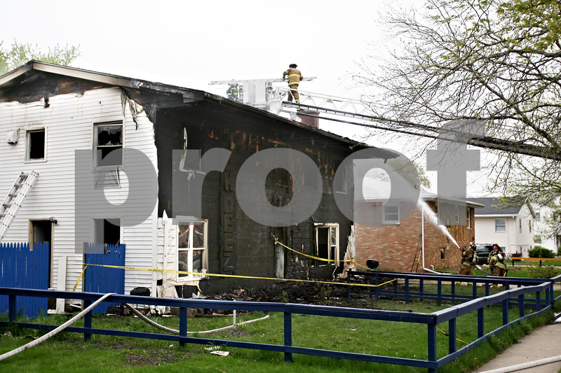 Beck Diefenbach  -  bdiefenbach@daily-chronicle.com<br /> <br /> Firefighters work around the fire damaged Omega Delta Fraternity house on the 800 block of Hillcrest Road in DeKalb, Ill.