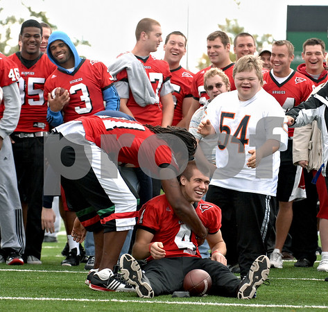 NIU Football's Justin Anderson, left-center, helps his teammate, kicker Ryan Salerno (seated) after Marc Isabel, right (no. 54) of Sycamore caused him to fall as he placed the ball on the tee during the Huskies' annual meeting with Special Olympics athletes on Sunday, October 4, 2009 in Dekalb. (Marcelle Bright/for the Daily Chronicle)
